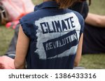 A climate change protestor wearing a top with climate revolution painted on