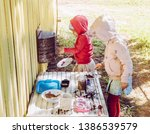 Small photo of Two young girls sisters play outdoors in so called mud kitchen, where you can make fake food, play with sand, dirt, water, plants and make a mess, it develops imagination and exploration.