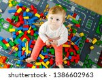 adorable baby girl playing with ... | Shutterstock . vector #1386602963