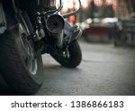 Part of a brand-new motorcycle with wheels and a dirty exhaust pipe. The motorcycle stands on the asphalt road in the dark evening and against the background the red light of the traffic light burns. - stock photo