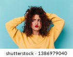 Small photo of Perky girl musses up curly hair with funny facial expression. Shot of woman with red lips on blue background