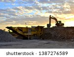 Small photo of Mobile Stone crusher machine by the construction site or mining quarry for crushing old concrete slabs into gravel and subsequent cement production