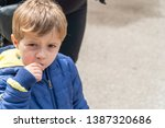 young boy eating popcorn at an... | Shutterstock . vector #1387320686