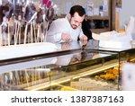 smiling american guy deciding... | Shutterstock . vector #1387387163