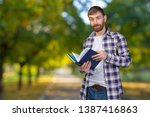 young man holding stack of... | Shutterstock . vector #1387416863