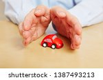 hands protect a little red car... | Shutterstock . vector #1387493213