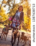 Stock photo dog walker woman enjoying with dogs while walking outdoors 1387638713