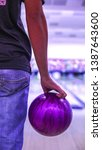 Small photo of A boy holding a purple bowling ball at the bowling alley get ready to strike. This sport or game is call ten-pins bowling.