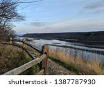 View of Mississippi River with wooden fence and Rocky trail with bluffs in background and dusk sky on top of Brady