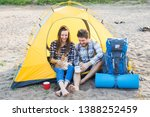 Stock photo pet summer tourism and nature concept young couple sitting with cat near a tent 1388252459