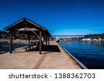 Small photo of Parry Sound Harbor - Covered wooden picnic shelter featuring the words PARRY SOUND, at the end of the pier, looking back toward the town of Parry Sound, and the railway trestle bridge.