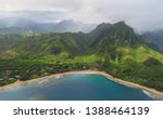 Aerial view over blue bay, golden beach, green mountains and misty clouds in Na Pali Coast State Wilderness Park, landscape photo taken from a helicopter, Kauai, Hawaii, USA - stock photo