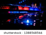 Small photo of Emergency warning red and blue roof mounted police LED blinker light bar turned on