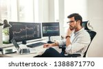 Small photo of Trading online. Successful and young bearded trader in eyeglasses and formal wear working with laptop while sitting in his office in front of computer screens with trading charts