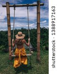 Small photo of travel series. Fashion photo of beautiful woman with dark hair in yellow dress posing on the swing with Bali jungle view