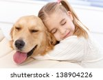 Stock photo lovely little girl hugging pet dog with passion eyes closed 138904226