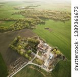 Small photo of Aerial view of farmstead and sawmill surrounded by green fields, vertical panorama