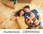 Small photo of The young happy couple is moving into a new house. They are lying down on the floor with their little puppy after they brought boxes with things to their new home.