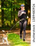 Stock photo girl running with dog outdoors in nature on a path in forest sunny day countryside copy space for 1389480926
