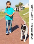 Stock photo pretty little girl walking a dog outdoors 138948686