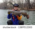 A large fat brown flathead catfish being held horizontally by a smiling woman sitting in a canoe in a blue and gold dry suit on a blue river in winter.