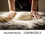 Small photo of Beautiful and strong men's hands knead the dough from which they will then make bread, pasta or pizza. A cloud of flour flies around like dust. Food concept.
