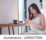 young happy asia woman using... | Shutterstock . vector #1390077500