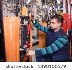Small photo of rapt male choosing fishing rod for fishing in the sports shop indoors