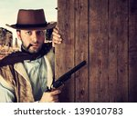 Bad gunman in the old wild west indicates with the gun a wooden plank - stock photo