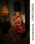 Beautiful traditional Indian girl sitting on sofa wearing ethnic bridal outfit with heavy makeup and gold jewelery, indian bride portrait - Image