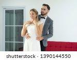 the groom wears a beautiful... | Shutterstock . vector #1390144550