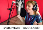 Female with microphone recording a voice for dubbing in music studio - stock photo
