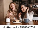 Stock photo image of excited happy pretty girls friends sitting in cafe drinking coffee eat cake 1390166750