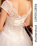 bridesmaid buttoning the dress... | Shutterstock . vector #1390513856