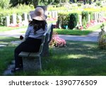 Woman Sits On A Bench In A...