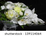 Elegant wedding bouquet made with white flowers on black piano - stock photo