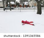 Small photo of Funny preschool child girl in warm clothes pink red jacket lying in snow during cold winter day with her face down. Upset kid doesn't want to go to school. Naughty cranky kid playing outdoors.