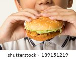 little boy eating a hamburger.... | Shutterstock . vector #139151219