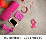 Small photo of Closeup on laying on the floor pink dumbbells, towel, bottle of water, headphones, fitness tracker, armlet, smartphone and pink ribbon shaped elastic band.