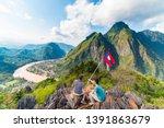 couple conquering mountain top... | Shutterstock . vector #1391863679