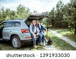 Senior couple sitting at the car trunk, enjoying nature while traveling in the young pine forest - stock photo