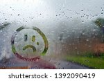 Small photo of Sad unhappy face drawn on fogged glass on a wet rainy grey window soft light grey skies