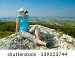 young woman on top of the rock - stock photo