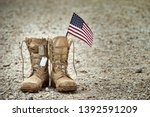 Old military combat boots with dog tags and a small American flag. Rocky gravel background with copy space. Memorial Day, Veterans day, sacrifice concept. - stock photo