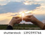 house in hands in the rays of... | Shutterstock . vector #1392595766