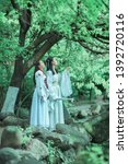 Two girls in white Chinese clothes hanfu are walking in the ancient garden