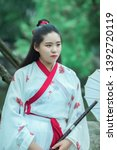 Girl in white Chinese dress hanfu walks in the ancient style garden