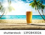Cold beer on wooden desk. Free space for your decoration. Landscape of beach with palms. Sunny summer day. Ocean landscape with blue sky. Beach party