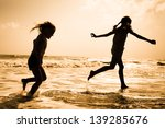 Two Kids Silhouettes Running On ...