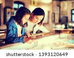 Small photo of Happy mother and daughter exploring expositions of previous centuries in museum
